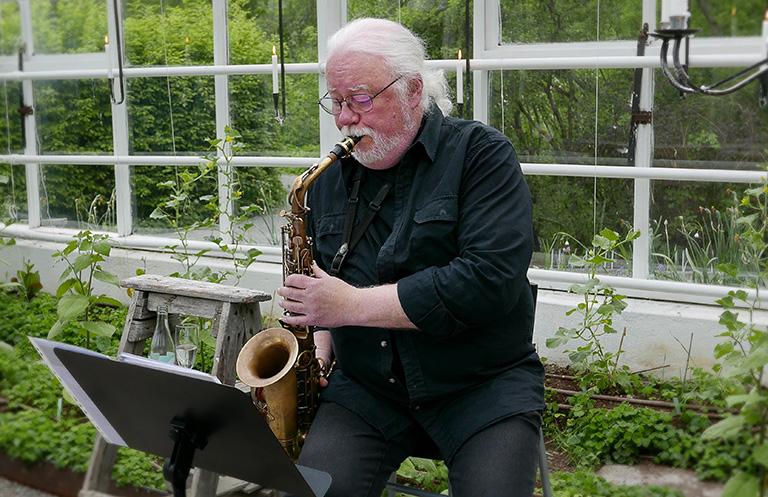 Anders Nystedt spelar saxofon på sommarmingel med tarte flambée med Galleri Andersson/Sandström på Rosendals Trädgård